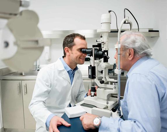 Eye doctor performing eye exam on patient