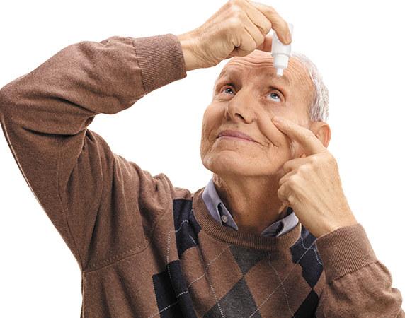Man putting eye drops in eye